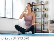 woman doing yoga in lotus pose at home. Стоковое фото, фотограф Syda Productions / Фотобанк Лори
