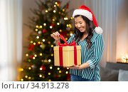 happy asian woman opening christmas gift at home. Стоковое фото, фотограф Syda Productions / Фотобанк Лори