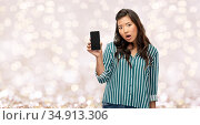 shocked asian woman with smartphone over lights. Стоковое фото, фотограф Syda Productions / Фотобанк Лори
