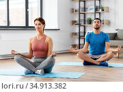 couple meditating in yoga lotus pose at home. Стоковое фото, фотограф Syda Productions / Фотобанк Лори