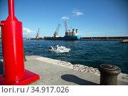 Croatia, Rijeka - Small motorboat leaves the port, behind a freighter. Редакционное фото, агентство Caro Photoagency / Фотобанк Лори
