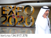 Dubai, United Arab Emirates, man in national costume walking past an advertising stand for Expo 2020 (2019 год). Редакционное фото, агентство Caro Photoagency / Фотобанк Лори