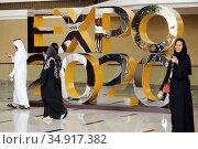 Dubai, United Arab Emirates, locals walk past an advertising display for Expo 2020 (2019 год). Редакционное фото, агентство Caro Photoagency / Фотобанк Лори