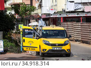 Yellow van stands on the special parking place for taxi cars. Vehicle with opened doors is waiting for passengers. Taxi service is in Alanya city. Turkey. Редакционное фото, фотограф Кекяляйнен Андрей / Фотобанк Лори