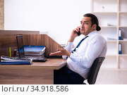 Young male employee unhappy with excessive work in the office. Стоковое фото, фотограф Elnur / Фотобанк Лори