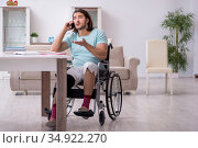 Young student in wheel-chair studying at home. Стоковое фото, фотограф Elnur / Фотобанк Лори