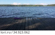 Preteen girl jumping from water and plashing, slow motion view. Wooden pier is on forest lake. Стоковое видео, видеограф Кекяляйнен Андрей / Фотобанк Лори