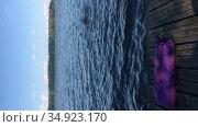 Девочка ныряет под воду в озере, полотенце на пирсе. Вертикальное видео. Стоковое видео, видеограф Кекяляйнен Андрей / Фотобанк Лори