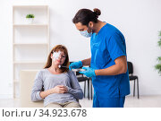 Young head injured woman visiting young male doctor. Стоковое фото, фотограф Elnur / Фотобанк Лори