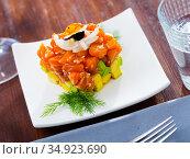 Cube of delicious salmon tartare garnish with avocado on plate at cafe. Стоковое фото, фотограф Яков Филимонов / Фотобанк Лори