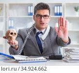 The businessman in the office smoking holding human skull. Стоковое фото, фотограф Elnur / Фотобанк Лори