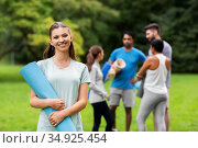 smiling woman with yoga mat over group of people. Стоковое фото, фотограф Syda Productions / Фотобанк Лори