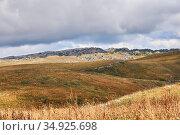Rocky mountain plateau with dry grass under cloudy sky. Стоковое фото, фотограф Евгений Харитонов / Фотобанк Лори