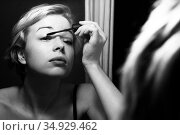 Woman getting ready for work doing morning makeup routine applying mascara in bathroom mirror at home. Beautiful caucasian girl applying eye make-up. Black and white image. Стоковое фото, фотограф Matej Kastelic / Фотобанк Лори