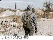 dangerous man stalker in mask, hood, backpack, holding a gun in his hand. Стоковое фото, фотограф Владимир Арсентьев / Фотобанк Лори