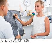 Boy with girl are writing on desk their homework on math. Стоковое фото, фотограф Яков Филимонов / Фотобанк Лори