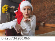 Portrait of woman in Santa hat blowing flying kisses at home. Стоковое фото, агентство Wavebreak Media / Фотобанк Лори