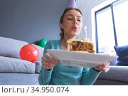 Woman blowing candle on cake at home. Стоковое фото, агентство Wavebreak Media / Фотобанк Лори