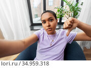 woman taking selfie and showing thumbs down. Стоковое фото, фотограф Syda Productions / Фотобанк Лори