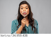 happy asian woman with magnifying glass on lips. Стоковое фото, фотограф Syda Productions / Фотобанк Лори