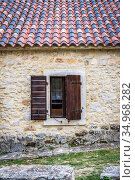 Window with wooden shutters on the wall of sandstone and a fragment of the roof with colored tiles (2018 год). Стоковое фото, фотограф Сергей Фролов / Фотобанк Лори
