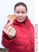 Young Caucasian woman with outstretched hand holding paper heart. Стоковое фото, фотограф Кекяляйнен Андрей / Фотобанк Лори