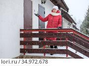 Realtor woman inviting to show the duplex house, standing close to entry door, winter season with snowfall. Стоковое фото, фотограф Кекяляйнен Андрей / Фотобанк Лори