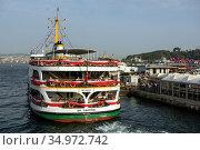 Cruise ship on the Golden Horn, as seen from the Galata Bridge. View of the Kadikoy Wharf. City of Istanbul, Turkey. Редакционное фото, фотограф Bala-Kate / Фотобанк Лори