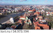 Scenic view from drone of Gothic buildings of Cathedral of St. John Baptist and Collegiate Church of Holy Cross and St. Bartholomew on Ostrow Tumski on sunny day, Wroclaw, Poland. Стоковое видео, видеограф Яков Филимонов / Фотобанк Лори