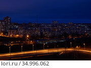 Night cityscape with illuminated road in the foreground and residential areas in the background. Стоковое фото, фотограф Евгений Харитонов / Фотобанк Лори