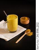 Стеклянная чашка с целебным индийским напитком золотое молоко с куркумой, с добавлением кардамона, имбиря, корицы и душистого перца. Металлическая трубочка для питья. Черный фон. Стоковое фото, фотограф Наталья Гармашева / Фотобанк Лори