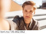young man or teenage boy taking selfie in city. Стоковое фото, фотограф Syda Productions / Фотобанк Лори
