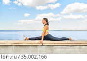 young woman doing full split at seaside. Стоковое фото, фотограф Syda Productions / Фотобанк Лори