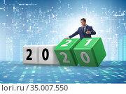 Businessman turning the year from 2020 to 2021. Стоковое фото, фотограф Elnur / Фотобанк Лори