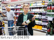 mature woman with glasses chooses bottle of wine in alcohol section of supermarket. Стоковое фото, фотограф Татьяна Яцевич / Фотобанк Лори