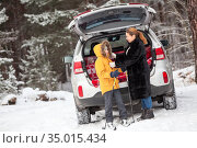 Mother dress her child for skiing while standing close to opened back door of car, cold weather in winter season. Стоковое фото, фотограф Кекяляйнен Андрей / Фотобанк Лори
