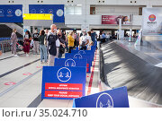Passengers wait baggage between dividing boards in the Antalya International airport. Signs with notification about keeping social distance during Covid-19 pandemic. Редакционное фото, фотограф Кекяляйнен Андрей / Фотобанк Лори