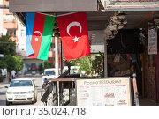 The national flag of the Republic of Azerbaijan and the Turkish flag hang in cafe or restaurant on the urban street. Decorated city streets. Alanya, Turkey (2020 год). Редакционное фото, фотограф Кекяляйнен Андрей / Фотобанк Лори