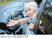 Uncomprehending lady driver makes a helpless gesture while sitting inside car after road accident with a motorcycle. Стоковое фото, фотограф Кекяляйнен Андрей / Фотобанк Лори