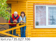 A happy mature couple is standing on the porch of a new wooden house with a bucket of apples. Стоковое фото, фотограф Акиньшин Владимир / Фотобанк Лори