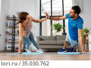 happy couple make high five in side plank at home. Стоковое фото, фотограф Syda Productions / Фотобанк Лори