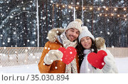 happy couple with red hearts at ice rink in winter. Стоковое фото, фотограф Syda Productions / Фотобанк Лори