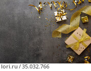 New Year concept. Bright gifts with gold ribbon, streamer and confetti on dark. Space for text. Top view. Стоковое фото, фотограф Сергей Молодиков / Фотобанк Лори