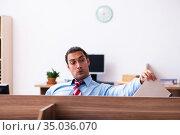 Young male employee in industrial espionage concept. Стоковое фото, фотограф Elnur / Фотобанк Лори