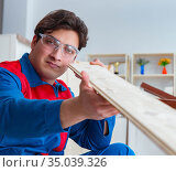 Young carpenter working with wooden planks. Стоковое фото, фотограф Elnur / Фотобанк Лори