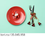 Round red ceramic plate, knife and fork on green background, festive... Стоковое фото, фотограф Natalya Danko / easy Fotostock / Фотобанк Лори