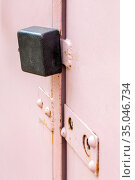 An iron padlock hangs on the doors of a metal street garage. Стоковое фото, фотограф Акиньшин Владимир / Фотобанк Лори