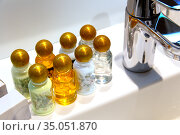 Modern faucet and ceramic sink in bathroom. Vials with various shampoos and oils. Стоковое фото, фотограф Евгений Ткачёв / Фотобанк Лори