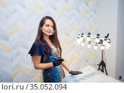 A woman with dark hair, permanent makeup artist, stands with a device in her hands at her workplace. Стоковое фото, фотограф Екатерина Кузнецова / Фотобанк Лори