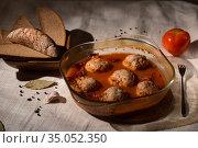 Meatballs in tomato sauce in a glass dish, rye bread, linen tablecloth, Low key. Стоковое фото, фотограф Ирина Мойсеева / Фотобанк Лори
